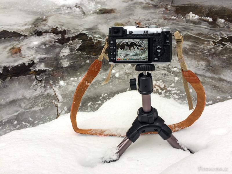 Bezzrcadlovka Fujifilm X-E2 na malém stativu při focení zamrzlých detailů v potoce.
