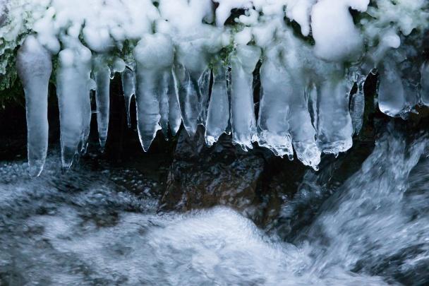 Tekoucí voda v zamrzlém potoce.