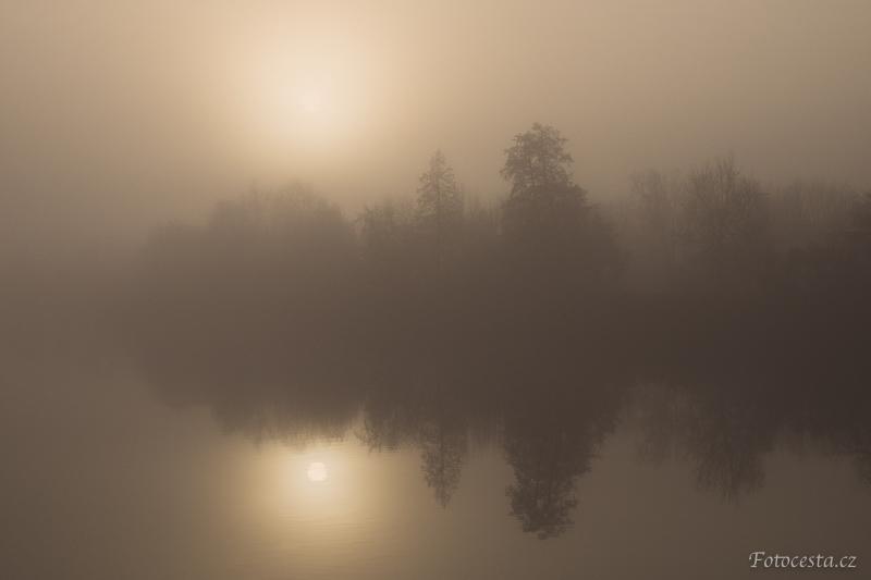 Mlhavý východ slunce nad rybníkem.