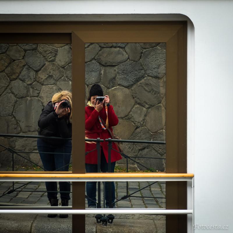 Odraz v zrcadlových dveřích lodě na pražské náplavce.
