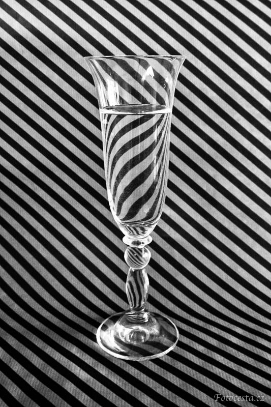 Odraz pruhů ve sklenici s vodou.