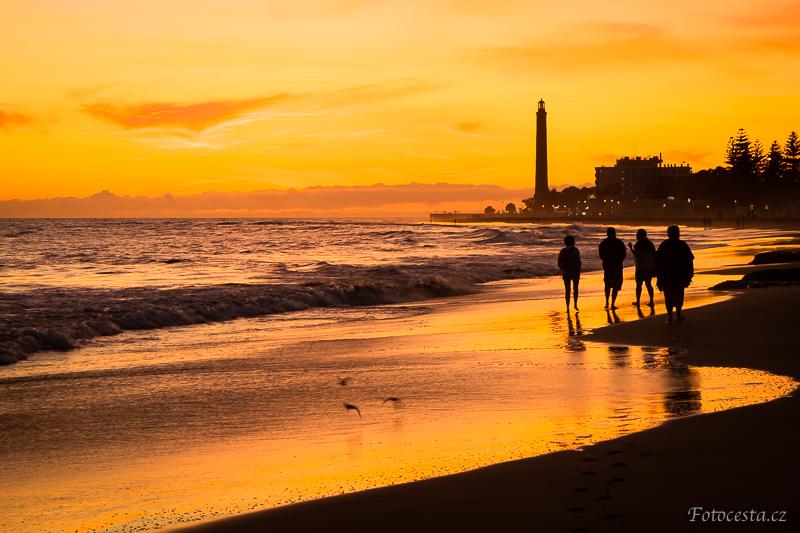 Siluety lidí při západu slunce na pláži v Maspalomas.
