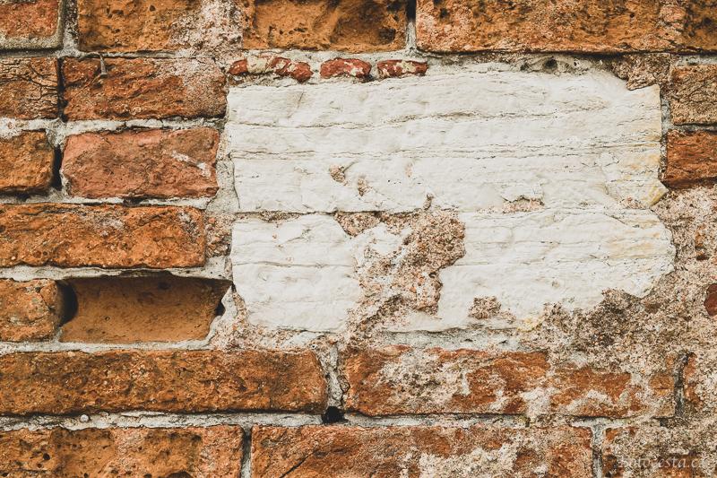 Popraskaná cihlová zeď.